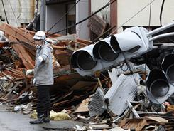 A construction worker controls traffic at a devastated area in Kesennuma, Miyagi, in northern Japan on Wednesday.