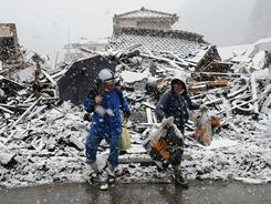 Snow falls as two people cross the street in Kamaishi, Iwate Prefecture, on Wednesday. Charities in the U.S. have raised $49 million in the six days since the tsunami hit Japan.