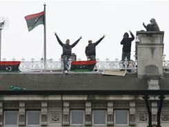 """Protesters gesture on the roof of the Libyan Embassy in London March 16.Some banners on the roof read """"Gadhafi No More."""""""