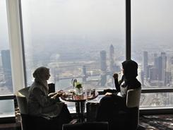 "Two women eat snacks at ""At.mosphere""  the world's highest restaurant  in Dubai, United Arab Emirates, on Jan 23."