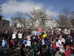Pro-labor protesters rallied Saturday at the state Capitol in Madison, Wis. They pledged to fight back after the governor signed a controversial bill into law.