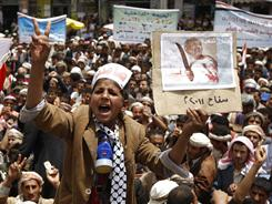 "A Yemeni boy shouts slogans while holding a picture of President Ali Abdullah Saleh with the slogan ""The killer of his people. The butcher of 2011"" during an anti-government protest in Sanaa on Wednesday."
