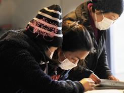 People check lists to find out about the safety of their relatives and friends at a shelter in Kesennuma in northern Japan on Friday.