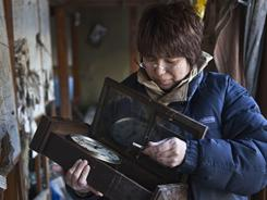 A woman looks through her belongings inside her home Friday in Ishinomaki, Japan.