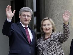 U.S Secretary of State Hillary Clinton, right, and Canadian Prime Minister Stephen Harper wave during a crisis summit Saturday at the Elysee palace in Paris.