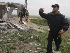 A Palestinian Hamas member inspects damage after an Israeli strike in east of Gaza strip, Saturday. Israeli police say Hamas militants in Gaza launched the heaviest shelling in more than two years.