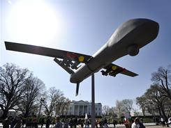 Anti-war protesters display an effigy of an attack drone in Saturday's demonstration in front of the White House.
