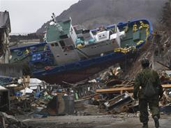 A Japanese soldier stops to look at a ship that is blocking a road Sunday in Onagawa, Miyagi Prefecture, northeastern Japan.