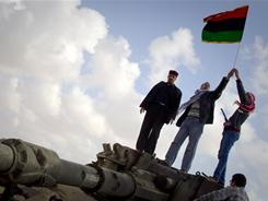 Libyan men celebrate on a destroyed tank belonging to the forces of Moammar Gadhafi in the outskirts of Benghazi on Sunday.
