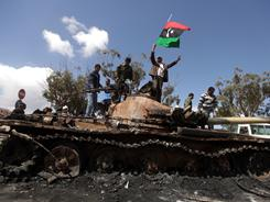 Libyan rebels wave their flag Sunday on top of the charred remains of a wrecked tank belonging to Moammar Gadhafi's forces at the western entrance to Benghazi, Libya.