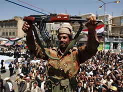 A soldier raises his weapon as he joins protests in Sanaa demanding the resignation of Yemeni President Ali Abdullah Saleh.