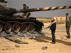 A tank that belonged to Gadhafi forces smolders in Shat al-Bedin, about 30 miles west of Benghazi.