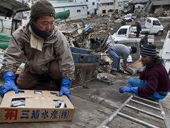 Men unload boxes of fish from the hold of a destroyed fishing boat in Kessenuma, Japan.The fish were still frozen and were being donated to relief efforts.