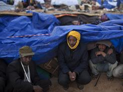 Men from Bangladesh, who used to work in Libya and fled the unrest in the country, take shelter under plastic sheet during a storm at a refugee camp at the Tunisia-Libyan border.