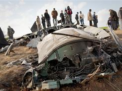 Libyans inspect the wreckage of U.S. fighter jet after it crashed in an open field in the village of Bu Mariem.