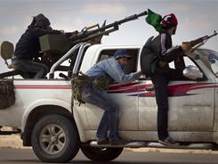 Libyan rebels retreat as mortars from Moammar Gadhafi's forces are fired on them on the outskirts of the city of Ajdabiya.