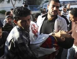 Palestinians carry one of four dead bodies to the morgue of Shifa Hospital in Gaza City, following an Israeli military strike Tuesday.