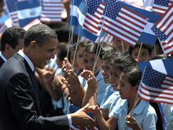 President Obama greets students at the United States of America School Center at the San Salvador airport Tuesday.