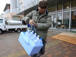 A man carries bottles of water after he got water from a supply water tank in earthquake-damaged Urayasu, Chiba prefecture, near Tokyo.