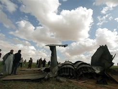 Libyans gather around the wreckage of a U.S. F-15 fighter jet in southeastern Benghazi, after crashing on a mission against Moammar Gadhafi's air defenses. 