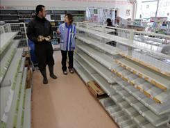 A Japanese man talks with a worker in a supermarket in the outskirts of the tsunami-damaged city of Rikuzentakata, in Iwate prefecture.