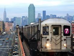 The No. 7 train runs through the Queens borough of New York with the Manhattan skyline in the background.