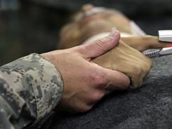 A chaplain prays over a wounded American soldier at the military hospital at Kandahar Airfield, Afghanistan.