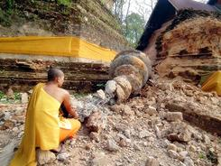 A Thai Buddhist monk inspects a fallen stupa of the Chedi Luang pagoda a day after a strong earthquake struck Myanmar near the Thai border.