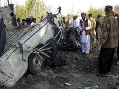 Pakistani officials visit the site of an explosion Friday in Lower Dir. Two police officers were killed and two others were injured when their patrol vehicle was hit by a roadside bomb attack, police said.