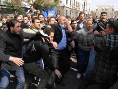 Anti-Syrian government protesters, left, and pro-government, right, clash after Friday prayers in Damascus.