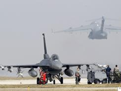 U.S. F-16 fighter jets are seen on the tarmac after landing as a C-17 plane takes off at the NATO air base in Aviano, Italy.