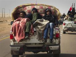 Libyan rebels travel on the road between Al-Egila and Ras Lanouf, a major oil port. Rebel forces have regained two oil complexes along the coast.