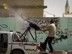 A Libyan rebel fires a gun in the city of Ajdabiya on Saturday. Rebels regained control of the eastern gateway city after international airstrikes on Moammar Gadhafi's forces.