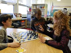 "Ryan Bonhote, 9, left, and David Beaudouin, 9, talk to Wendi Fischer, aka, the ""Chess Lady,"" at William J. McGinn Elementary School in Scotch Plains, N.J."