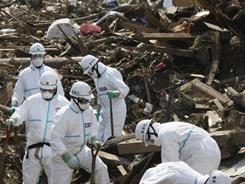 Tokyo Metro Police officers search for missing people Monday in Minamisoma, Fukushima Prefecture.