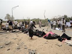 Yemenis lined up bodies after a massive blast killed dozens at an ammunition plant in southern Yemen.