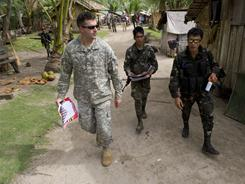 Philippine soldiers walk with U.S. Sgt. Scott Didion on Basilan island. The militaries have worked together since 2001.