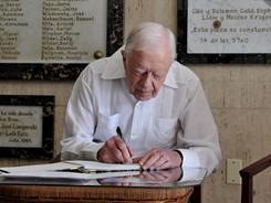 Jimmy Carter signs the guest book at the Jewish Community center in Havana.
