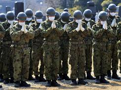 Members of the Japan Ground Self-Defense Force pray Tuesday for victims at a mass grave site in Yamamoto, Miyagi Prefecture.
