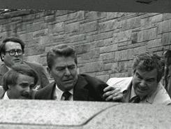 President Reagan is pushed into his limousine after he was shot in an assassination attempt by John Hinckley Jr. while leaving the Washington Hilton Hotel on March 30, 1981.