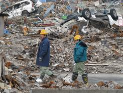 Rescue workers walk through the former fishing town of Yamada, where, so far, 444 bodies have been recovered and 3,821 people were living in shelters.