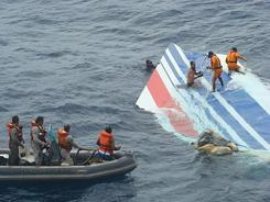 Recovery teams get ready to tow some of the initial pieces of wreckage on June 8, 2009.