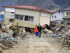 A couple walk Wednesday through the town that was burned by the March 11 earthquake and tsunami in Kesennuma, Miyagi Prefecture, northern Japan.