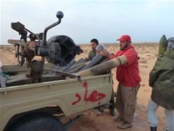 Rebels unpack and load a 106mm cannon into a truck outside of Ras Lanouf. The graffiti on the truck says jihad.