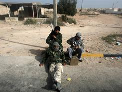 Libyan rebels rest east of Ras Lanouf on Wednesday after being pushed back by pro-Gadhafi forces.