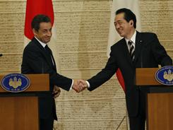 French President Nicolas Sarkozy and Japanese Prime Minister Naoto Kan shake hands during a joint press conference in Tokyo on Thursday.