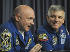 Mark Kelly, left, takes questions from the media regarding the next shuttle mission as pilot Gregory Johnson listens at Kennedy Space Center in Florida on Thursday.