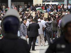 Jordanian police stand guard as pro-reform activists attend a rally outside the municipal offices in Amman on Friday.