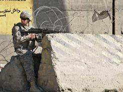 An Army soldier guards the site of a suicide attack in the main gate of U.S. military base Camp Phoenix in Kabul on Saturday.