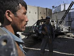 Afghan policemen keep watch near the wreckage of a burned-out vehicle at the U.N. headquarters in Mazar-i-Sharif on Saturday, after protesters attacked the compound Friday.